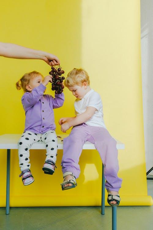 A Person Giving Their Children A Fresh Grape Fruit