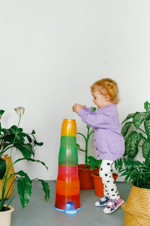 Girl in Purple Sweater Playing Beside Potted Plants