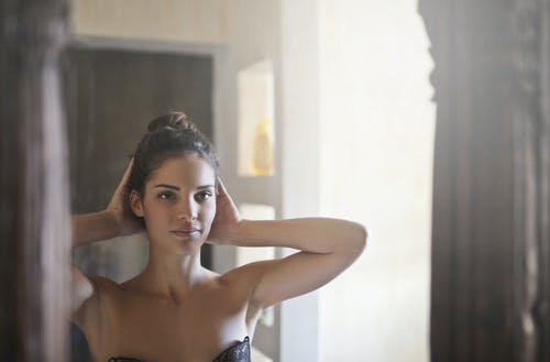Woman in Black Brassiere Looking Her Body on Mirror