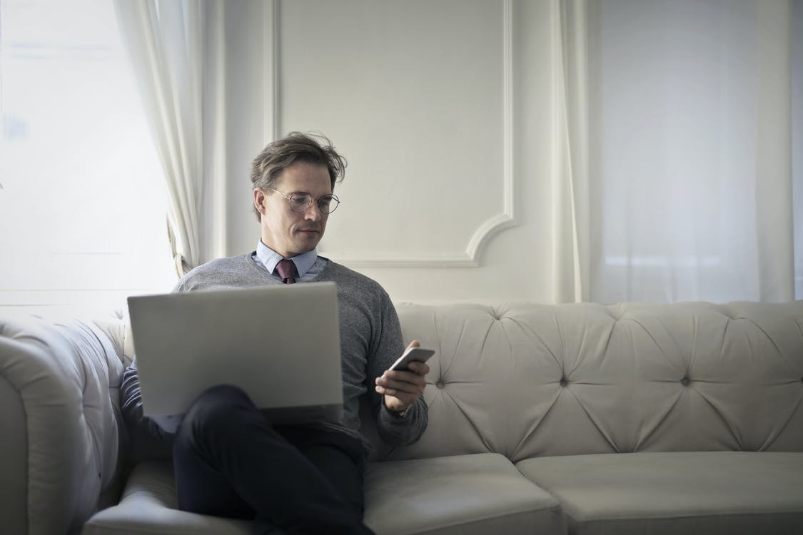 Photo of a Man Using Laptop And Cellular Phone