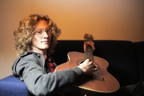 灰色外套的人彈棕色民謠吉他