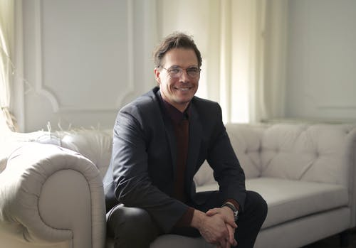 Smiling Man in Black Suit Wearing Eyeglasses Sitting on White Couch