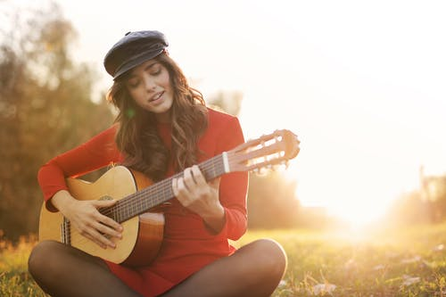 Woman in Red Long Sleeve Dress and Black Cap Sitting on Brown Grass Field Playing Guitar