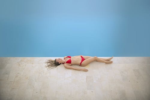 Woman in Red Bikini Lying on Floor