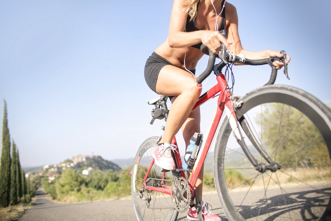 Female cyclist riding bicycle along mountain road in summer