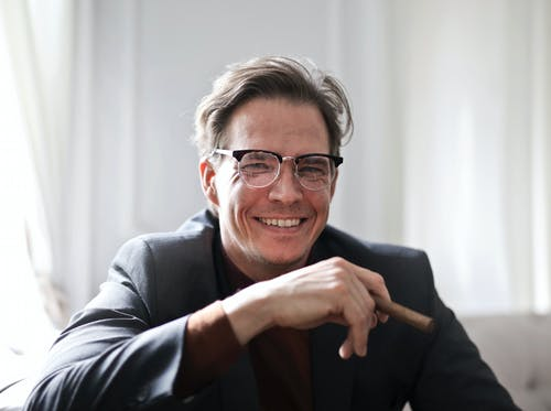 Adult man with cigar smiling at camera