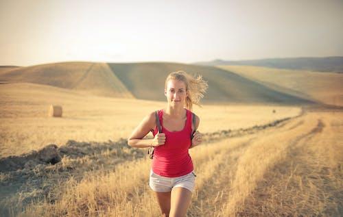 红色背心和白色短裤在棕色草地上行走的女人