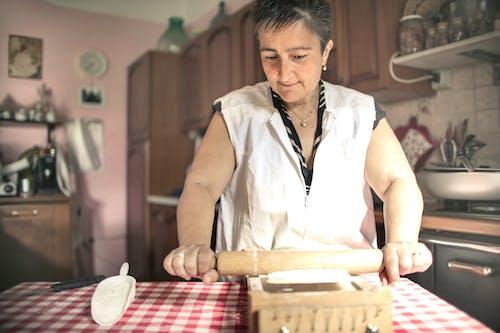 Senior woman rolling dough in kitchen