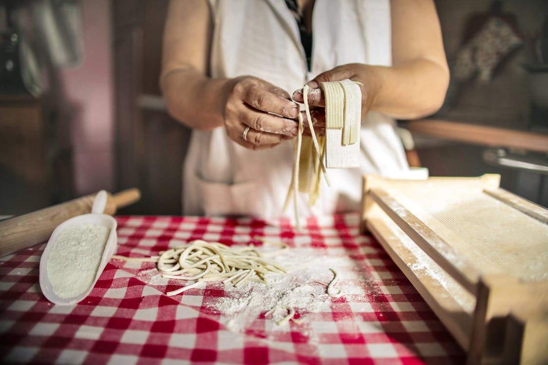Unrecognizable cook in uniform standing at table doing noodles from dough in kitchen at home