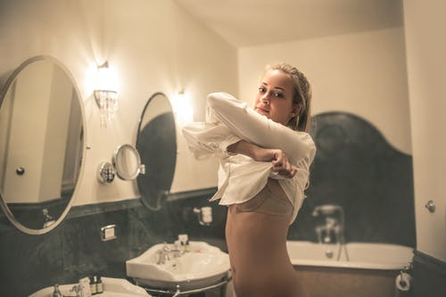 Woman taking off blouse in bathroom