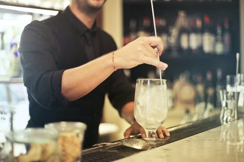 Crop barman making cocktail in pub