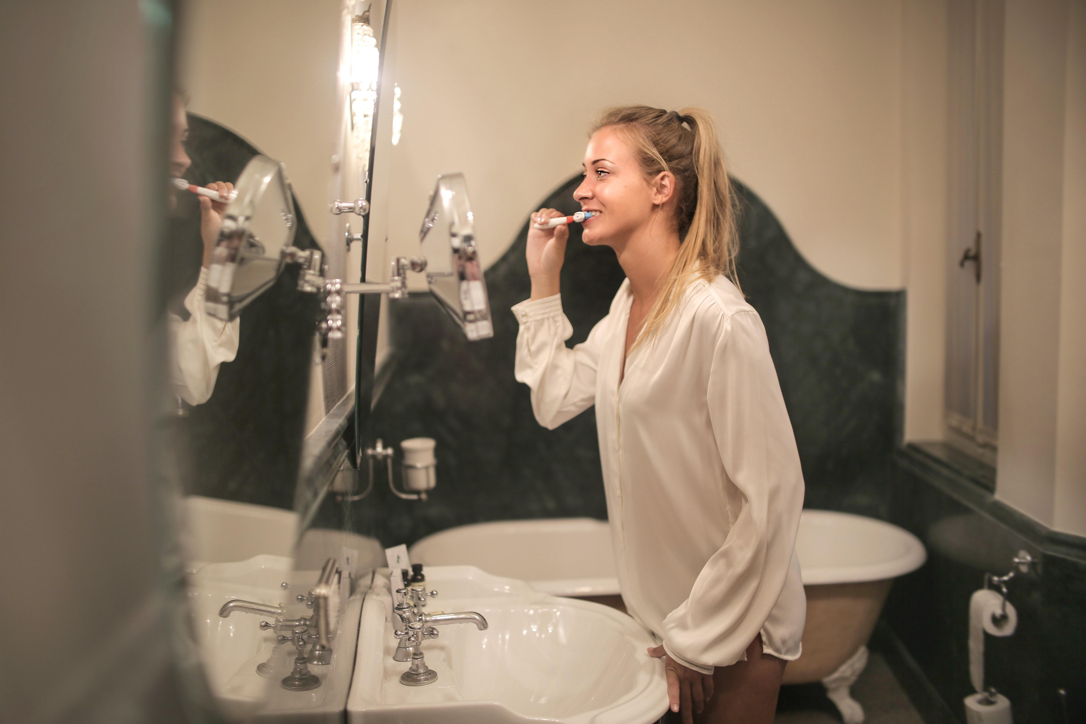girl brushing her teeth overbrushing