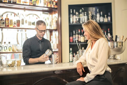 Modern young blonde in formal blouse resting at counter in bar watching barman making cocktail