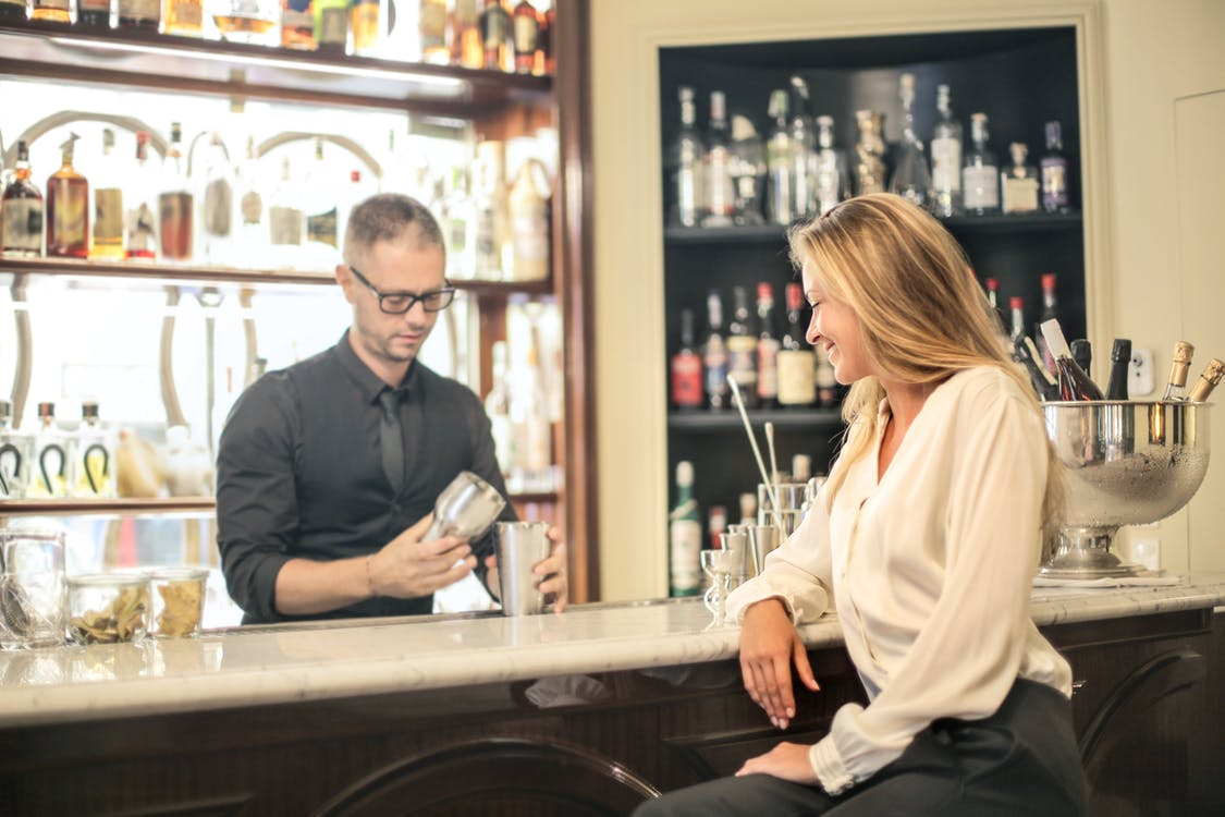 Elegant female sitting at counter waiting for bartender to prepare cocktail