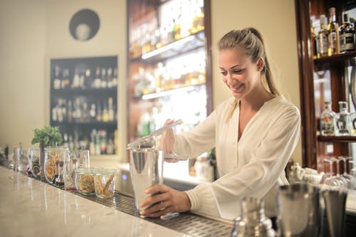 Smiling blonde in white blouse squeezing fresh juice into stainless shaker while preparing cocktail in bar