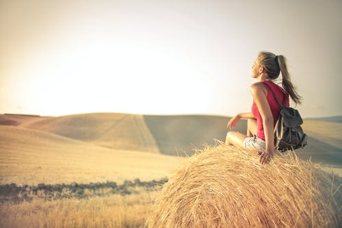 Woman in Red Tank Top Sitting on Brown Hay Roll Carrying Back pack