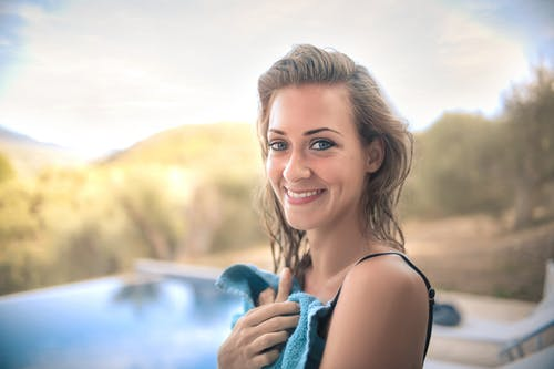 Cheerful woman with towel on poolside
