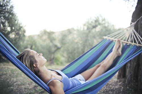 Woman in Blue Tank Top Lying on Blue and Green Stripped Hammock