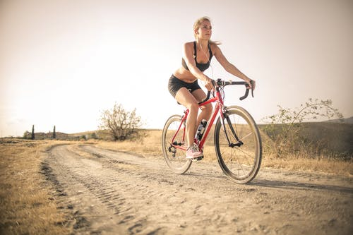 Woman in Black Tank Top and Black Shorts Riding Red Bicycle on Brown Sand