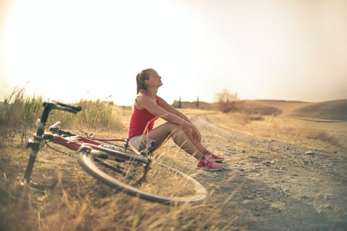 Full body of female in shorts and top sitting on roadside in rural field with bicycle near and enjoying fresh air with eyes closed