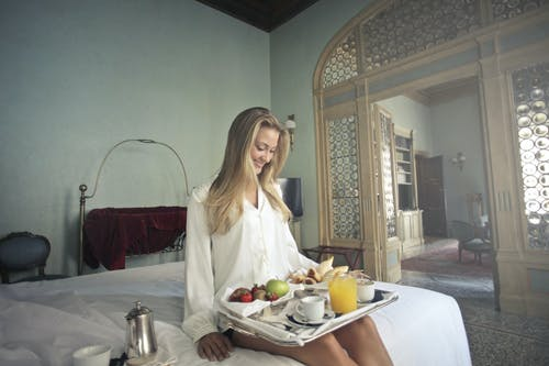 Cheerful woman with breakfast on tray in hotel bedroom