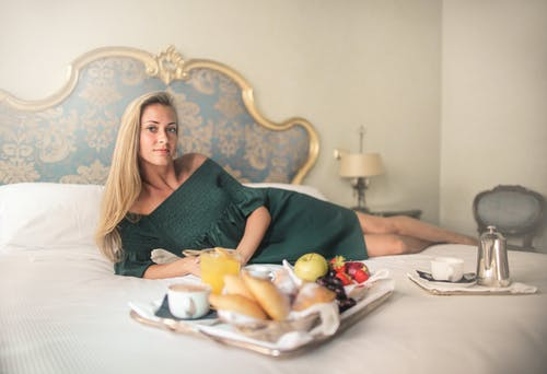 Calm blonde with tray of breakfast on bed in hotel room
