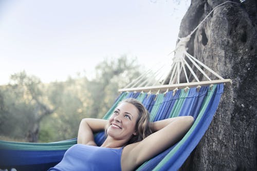 Woman in Blue Tank Top Lying on Blue Hammock Smiling