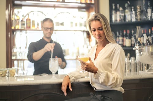Pensive woman with cocktail in bar