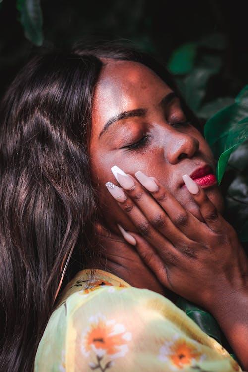 Gentle black woman touching face