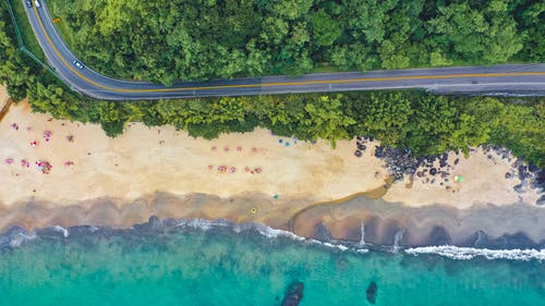 Drone view of tranquil turquoise water washing sandy beach with paved road running through tropical plants