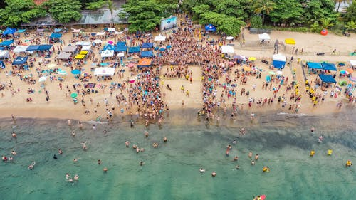 Drone view of crowded coast of tropical ocean with swimmers ready for competition