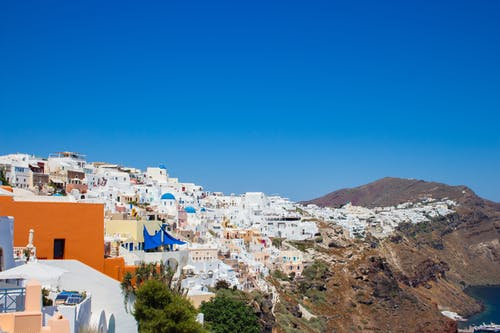 White and Brown Concrete Houses Near Mountain Under Blue Sky