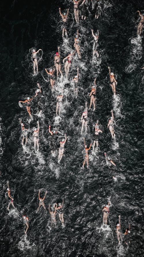 From above of many people taking park in swimming race and swimming forward in sea water