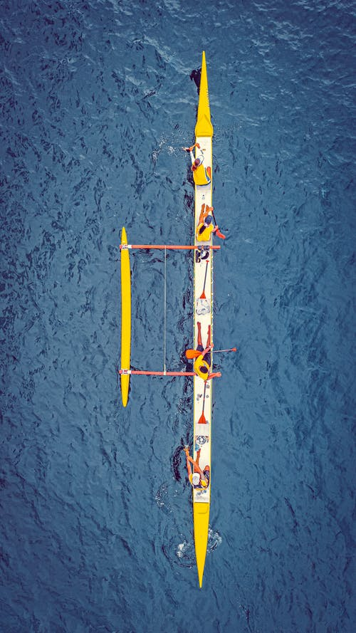 Rowers resting on boat in blue water