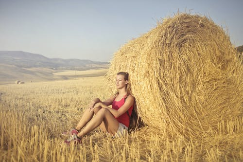 Woman in Red Tank Top Sitting on Brown Hay Field Leaning on Hay Roll