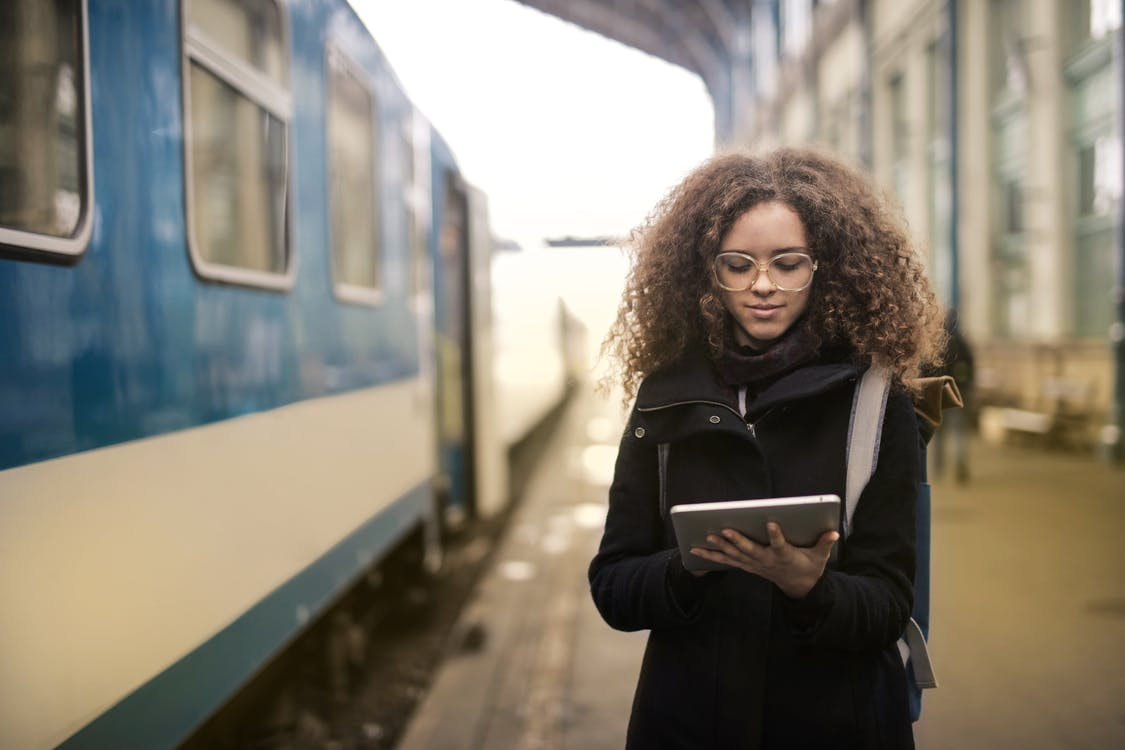 Woman in Black Coat Holding White Tablet Computer