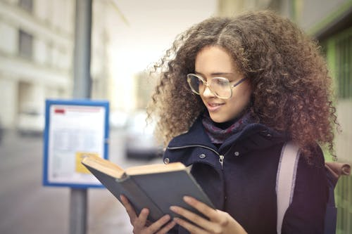 Woman with Curly Hair Wearing Eyeglasses Reading Book