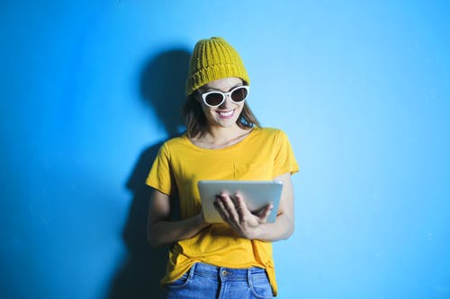 Woman in Yellow shirt Leaning Against Blue Wall