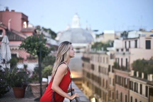 Woman in Red Sleeveless Dress Standing on Roof Top
