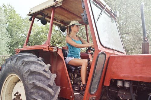 Woman in Blue Tank Top Driving a Red Tractor
