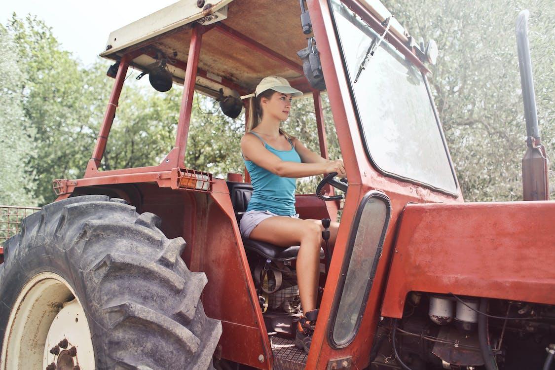 Kobieta W Niebieskim Podkoszulku Prowadzi Czerwony Traktor