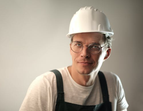 Content male builder in workwear and hardhat smiling on gray background in studio and looking at camera