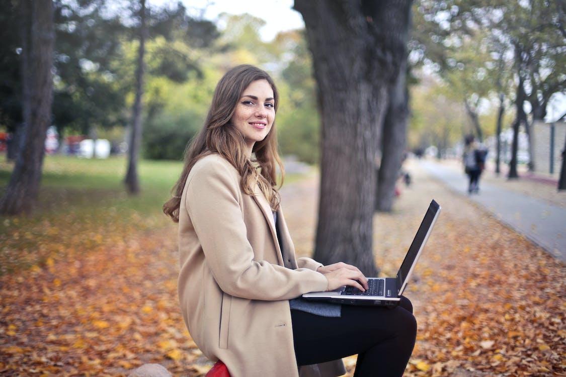 Joyful confident woman using netbook in park