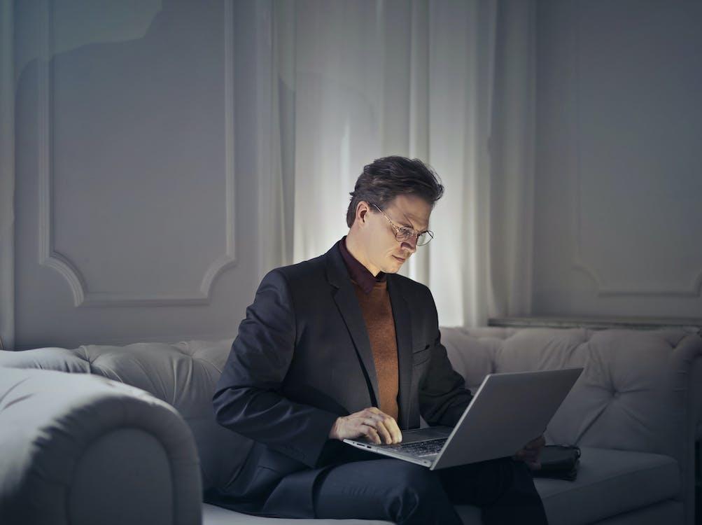 Man in Black Suit Wearing Eye Glasses Sitting on Gray Sofa Using Macbook