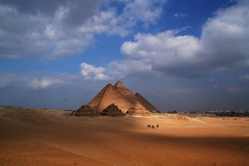 Amazing view of sandy dunes in desert with Pyramid of Cheops in Egypt