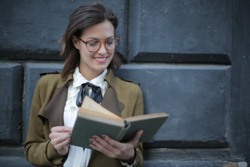 Happy adult woman reading book with interest on street