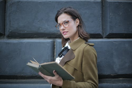 From below confident young female in glasses and elegant vintage clothes looking away and contemplating while reading rook on street near black wall of aged building in city