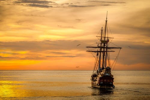 Brown Sailing Boat on the Sea during Sunset