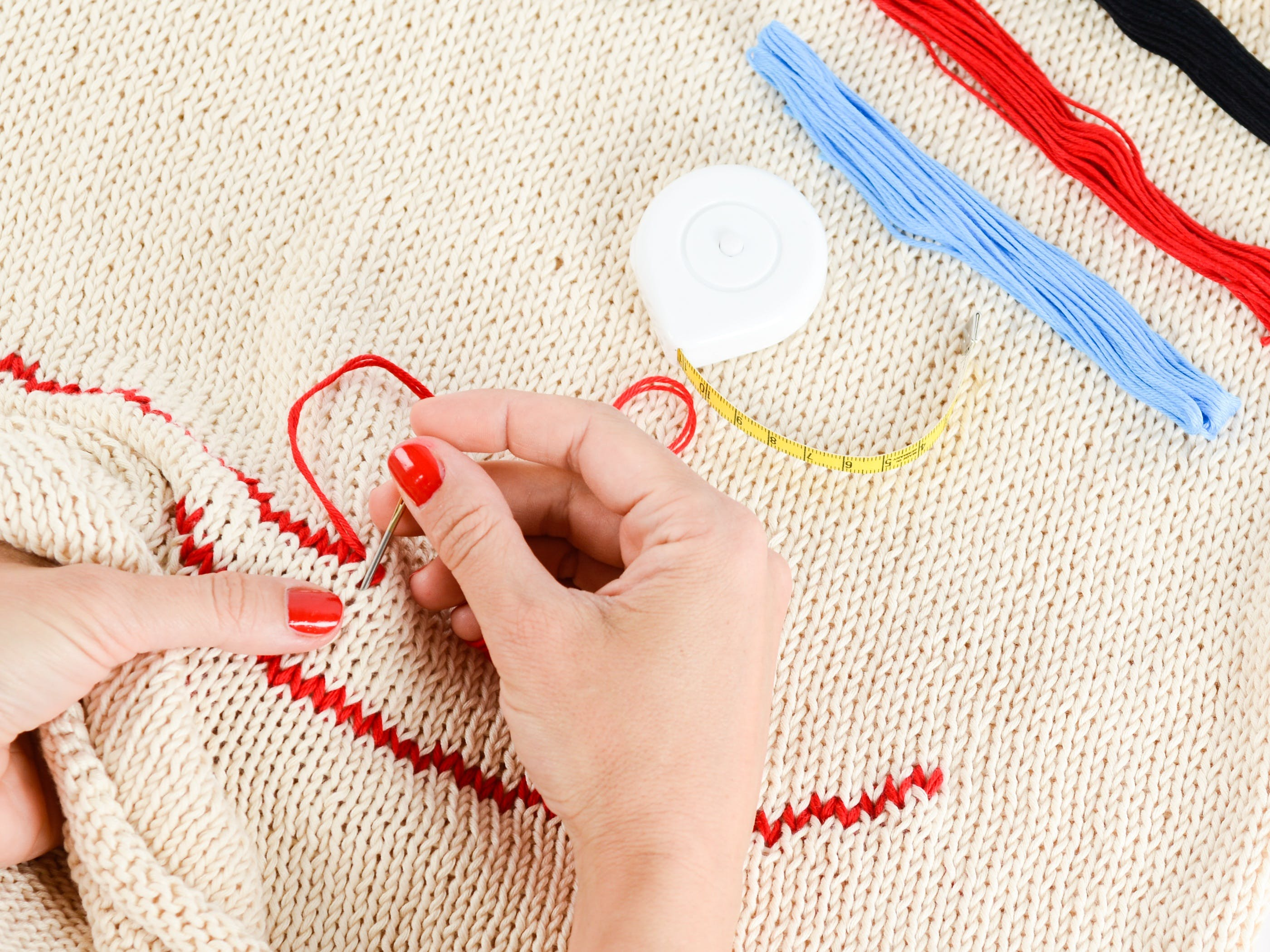 Person Embroidering a Beige Textile