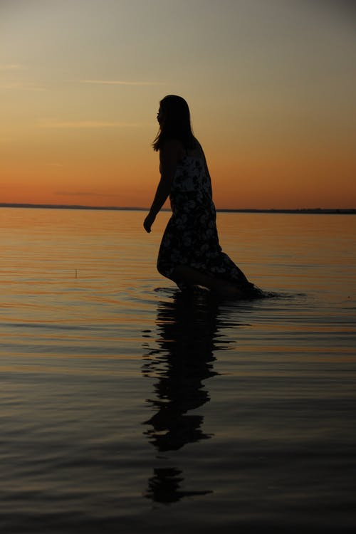 Silhouette Photo of Woman Standing on Water during Sunset